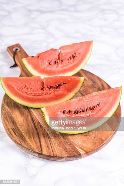 High-Angle View Of Sliced Watermelon On Wooden Chopping Board