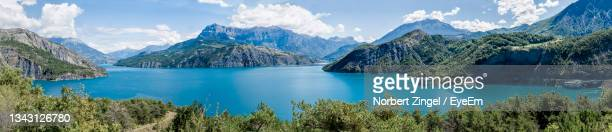 highest resolution panoramic shot of a branched turquoise  lake cloudy sky, mountains and greenery. - norbert zingel stock-fotos und bilder