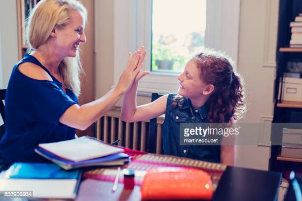 high-five between mother and daughter after finishing school homework at home. - pencil case stock photos and pictures