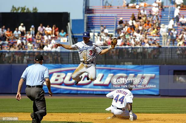 Highflying Los Angeles Dodgers' shortstop Cesar Izturis loses his grip on the ball as New York Mets' Mike Cameron dashes past to steal second in the...