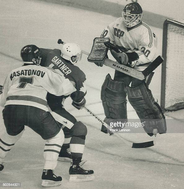Highflying stopper Soviet goaltender Evgeny Belosheikin jumps up to make a save with dangerous Mike Gartner of Team Canada buzzing around the net in...