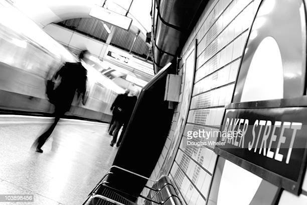 High-key black and white image of Baker Street Underground station in London England, tilted, with a moving train and moving businessman on display.