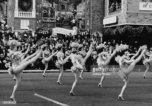 Highkicking young ladies during the Macy's Day Parade at Thanksgiving in New York City 26th November 1961 A number of tableaux behind commemorate...