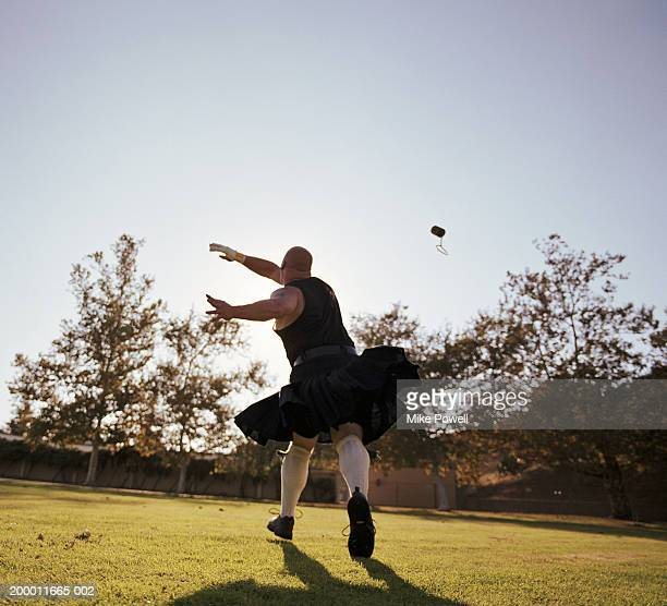 Highland Games, competitor throwing weight for distance, rear view