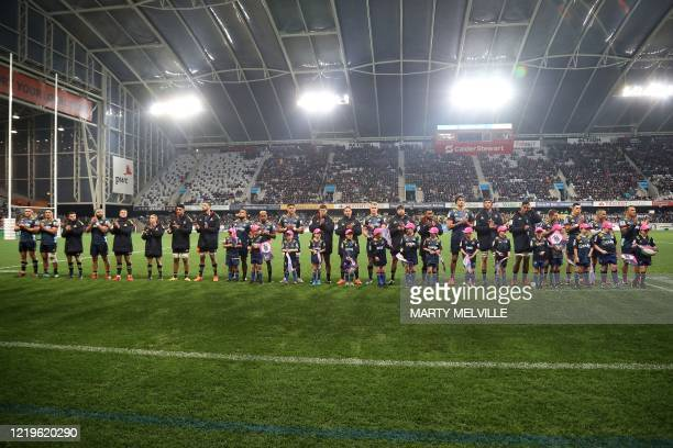 Highlanders players listen to a speech about the COVID-19 coronavirus before the Super Rugby match between the Otago Highlanders and Waikato Chiefs...