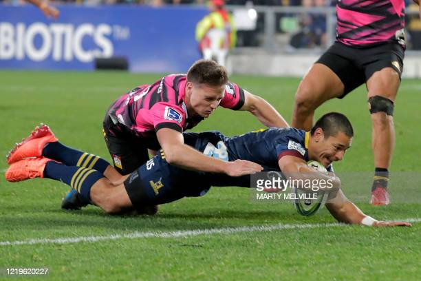 Highlanders' Sio Tomkinson scores a try in front of Chiefs' Kaleb Trask during the Super Rugby match between the Otago Highlanders and Waikato Chiefs...