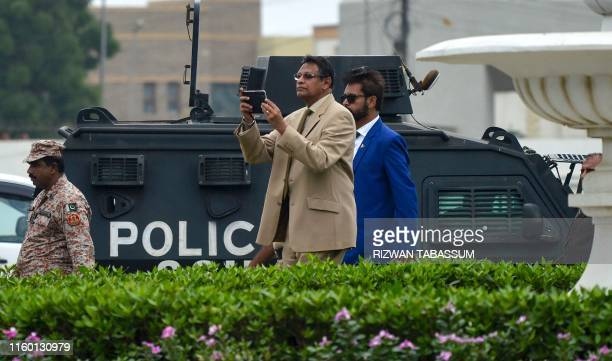 A highlevel security delegation member of Sri Lanka Cricket secretary Mohan De Silva takes images as he visits the National Cricket Stadium in...