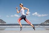 Highlighted leg bones of jogging woman on beach
