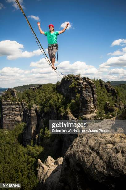 Highline athlete walking on slackline in mountains, Bad Schandau, Saxony, Germany