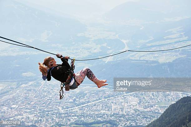 Highline walker hanging on tightrope, Innsbruck, Tyrol, Austria
