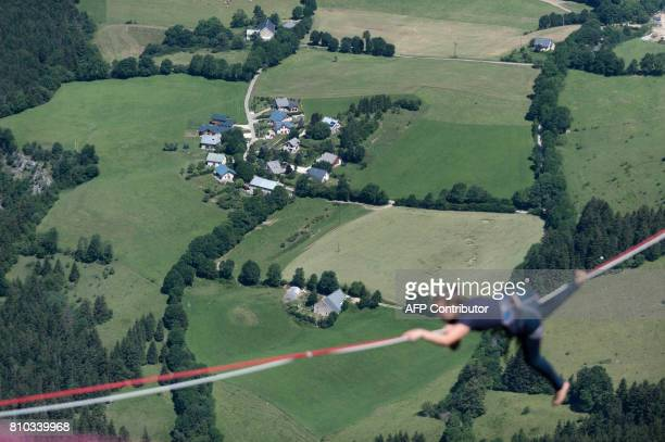 A highliner crawls on a slackline during the European 'Marmotte Highline Project' meeting on July 7 2017 in LansenVercors near Grenoble eastern...