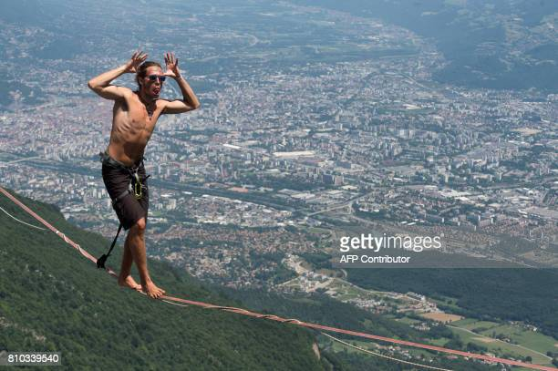 A highliner pulls a face as he walks on a slackline during the European 'Marmotte Highline Project' meeting on July 7 2017 in LansenVercors near...