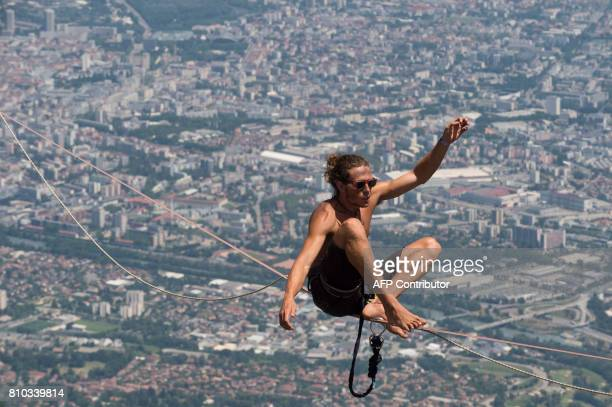 A highliner sits on a slackline during the European 'Marmotte Highline Project' meeting on July 7 2017 in LansenVercors near Grenoble eastern France...
