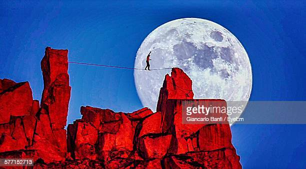 Highliner Walking On Rope Over Rocks Against Full Moon In Clear Sky At Sunset