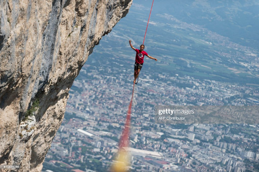 TOPSHOT - A highliner walks on a slackline during the European 'Marmotte Highline Project' meeting on July 7, 2017 in Lans-en-Vercors near Grenoble, eastern France. /