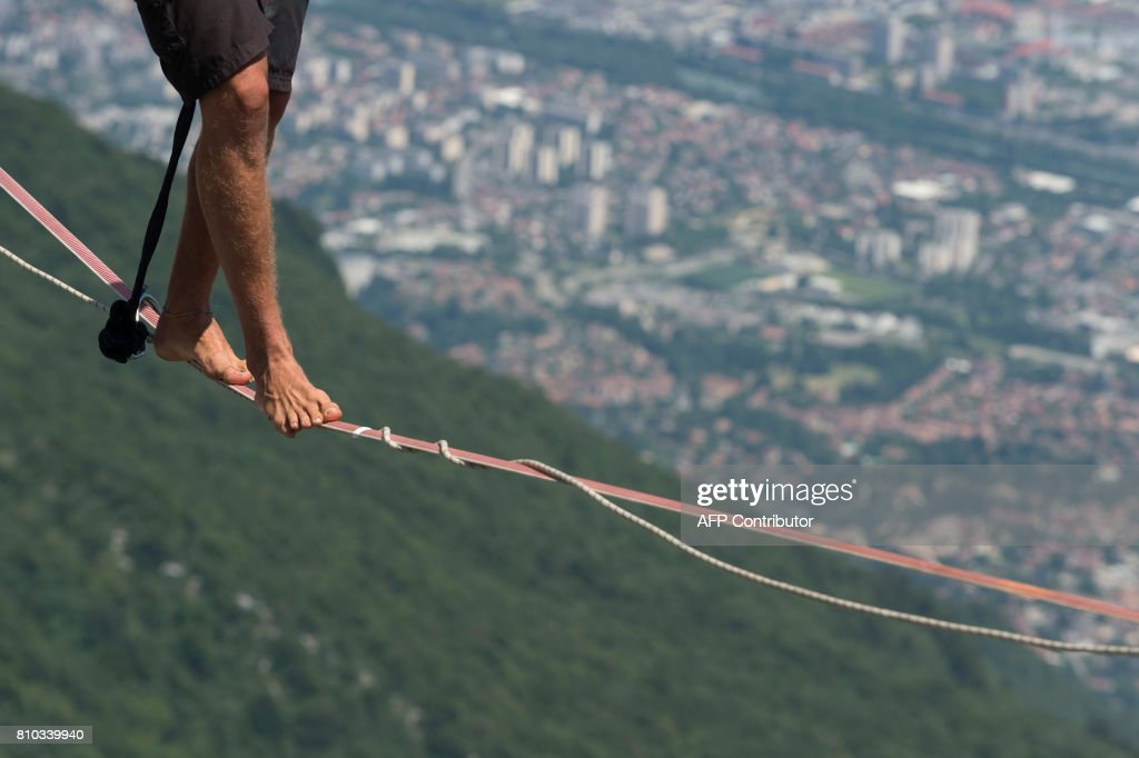 A highliner walks on a slackline during the European 'Marmotte Highline Project' meeting on July 7, 2017 in Lans-en-Vercors near Grenoble, eastern France. /