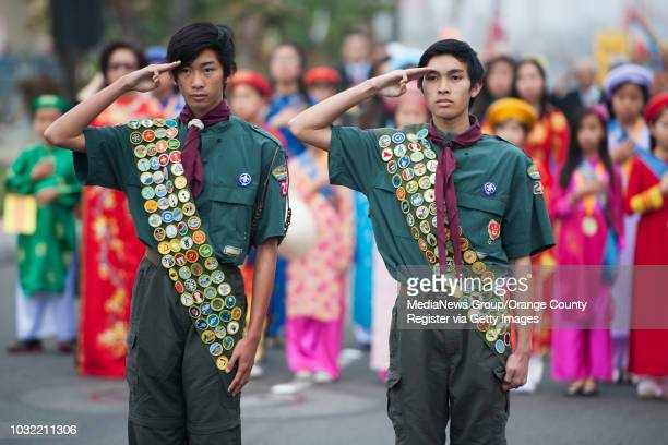 Highly decorated Boy Scouts Ben Nguyen left, and his brother Koby salute during the National Anthem before the start of the annual Tet Parade in...