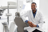 Highly qualified young dentist posing at modern clinic