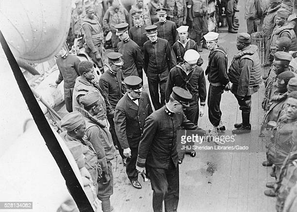 Highly ranked military officials inspecting African American sailors standing in lines leading official pointing to shoes of one soldier during World...