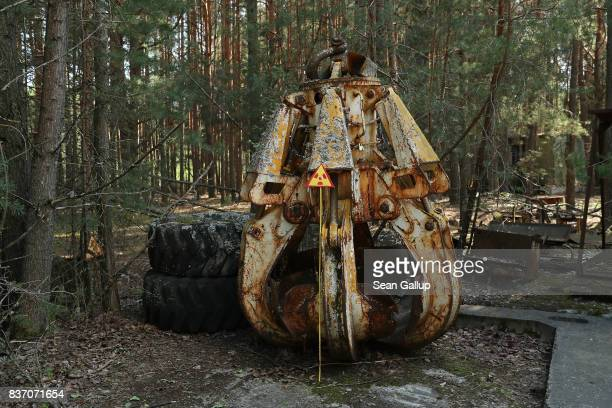 A highlyradioactive contaminated metal claw likely used in the postaccident cleanup stands on the ground in a forest on the outskirts of the ghost...