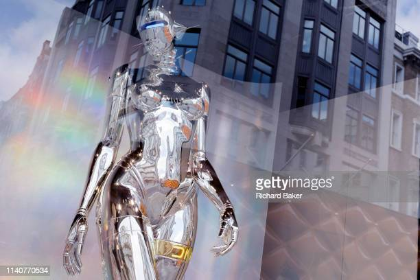 Highly-reflective silver-coloured mannequin in the window of the fashion brand Dior in New Bond Street, on 30th April 2019, in London, England.