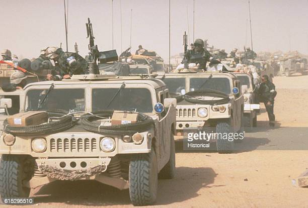 High-mobility, multipurpose, wheeled vehicles of the 1st Brigade, 101st Airborne Division, await orders to convoy into Iraq during Operation Desert...