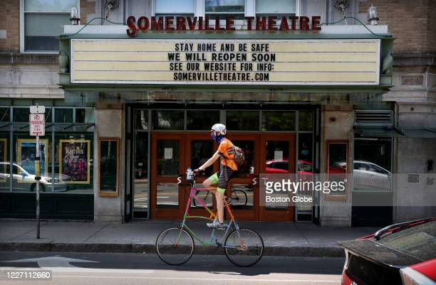 High-riding bike rider rides past The Somerville Theatre in Davis Square remains closed in Somerville, MA on July 11, 2020. Somerville officials...