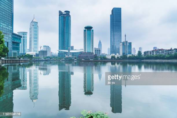 high-rise buildings by lake,wuhan - wuhan stock pictures, royalty-free photos & images
