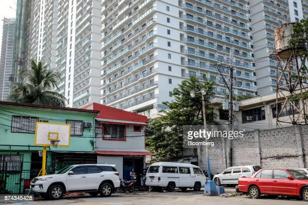 A highrise condominium stands behind lowcost housing in Mandaluyong Metro Manila Philippines on Tuesday Nov 14 2017 Economists are forecasting the...