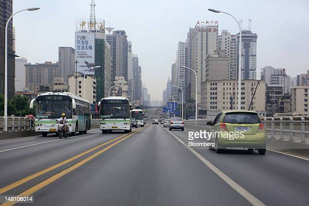 High-rise residential and commercial buildings stand as traffic moves along a road in Changsha, Hunan Province, China, on Sunday, June 24, 2012. The...