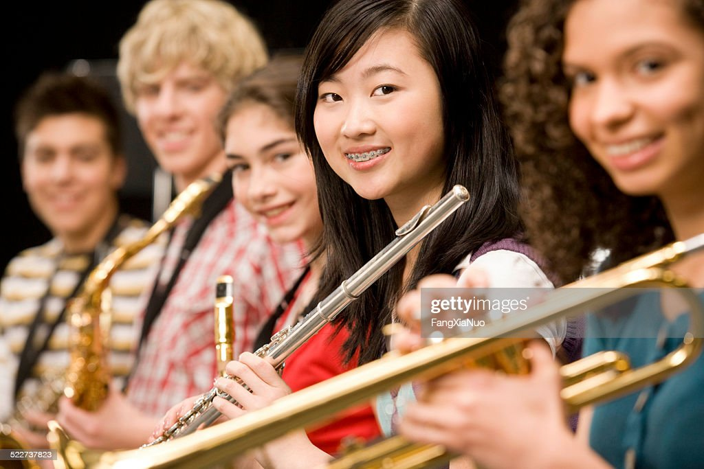 High-school girl playing flute with schoolmates : Stock Photo