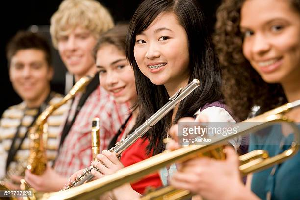 high-school girl playing flute with schoolmates - performance group stock pictures, royalty-free photos & images