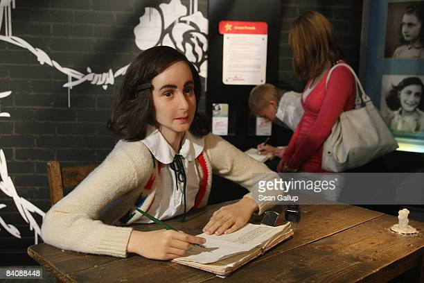 Highschool students write their thoughts about Anne Frank into a book behind a wax figure of Frank on the first public day of the Anne Frank figure...