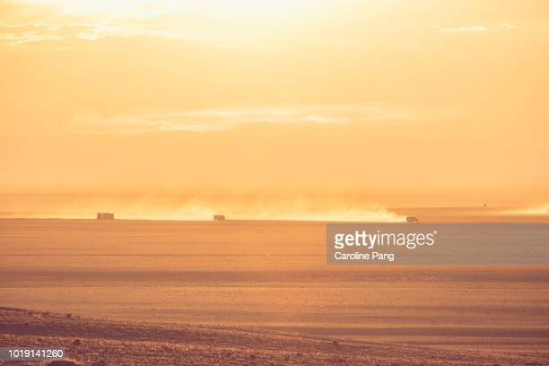 High-speed off-road vehicles with trails of dust on the Gobi desert at sunset.