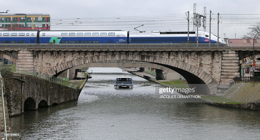 A TGV high-speed train crosses a bridge while the river shuttle 'Le Millenaire' sails on the Saint-Denis canal, on December 10, 2012, in Paris.