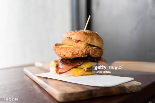 high-stacked burger stacked with different meats, chicken, beef, bacon and melted cheese, served on a wooden chopping board - ready to eat stock pictures, royalty-free photos & images