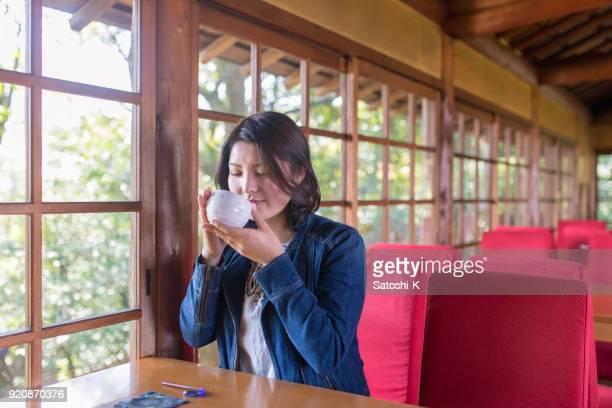午前中に日本茶を飲む高ティーンの女の子