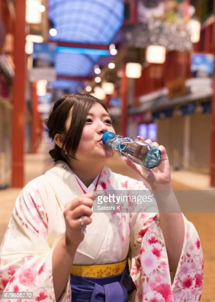 High-teen girl in Hakama drinking bottle of soda