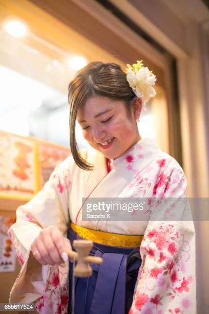 Hoge-tiener meisje in traditionele doek Hakama spelen Bilboquet