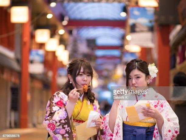 High-teen girls in Hakama eating fried chicken in shopping mall