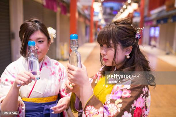 High-teen girls in Hakama looking at a bottle of soda