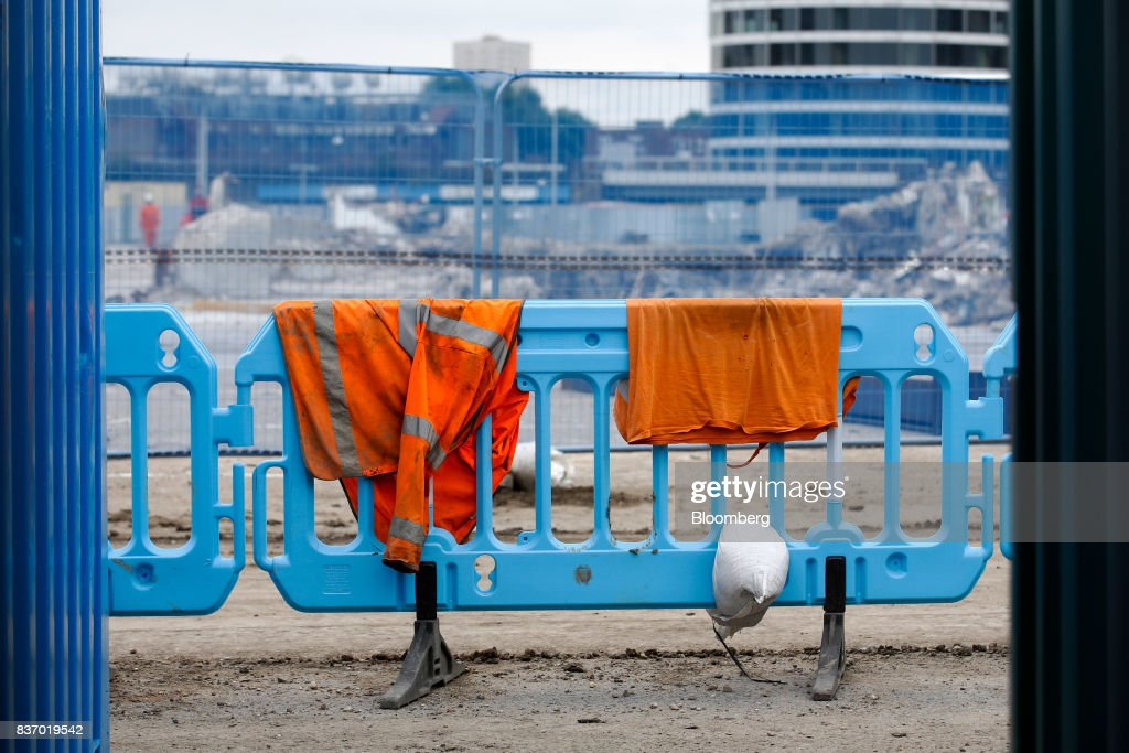 A high-visibility jacket and sandbag sit on fencing as demolition work takes place at the Nine Elms Square construction site in London, U.K., on Tuesday, Aug. 22, 2017. Billionaire Wang Jianlins Dalian Wanda Group Co. scrapped plans to buy the land plot in London for 470 million pounds ($606 million) amid the Chinese governments intensifying scrutiny of overseas investments. Photographer: Luke MacGregor/Bloomberg via Getty Images