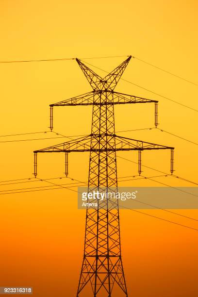 Highvoltage electricity pylon transmission tower silhouetted against sunset