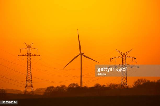 Highvoltage electricity pylons transmission towers and wind turbine silhouetted against sunset