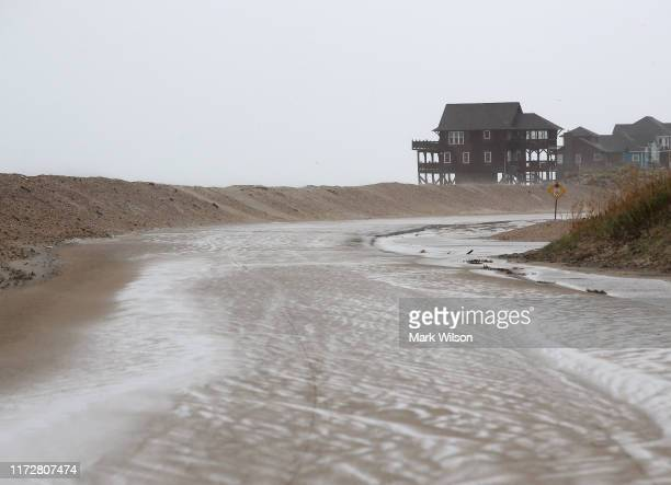 Highway 12 leading onto Hatteras Island is covered with sand after Hurricane Dorian hit the area on September 6 2019 in Mirlo Beach North Carolina...