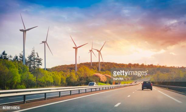 highway and wind turbines - energy efficient stock photos and pictures