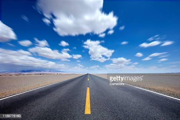 highway at gobi desert in blue day - 散歩道 ストックフォトと画像