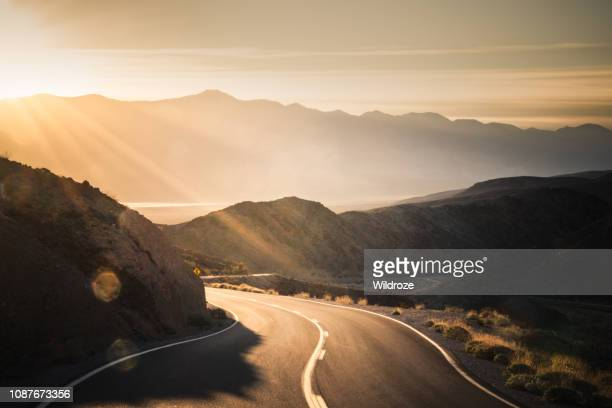 highway at sunrise, going into death valley national park - califórnia imagens e fotografias de stock