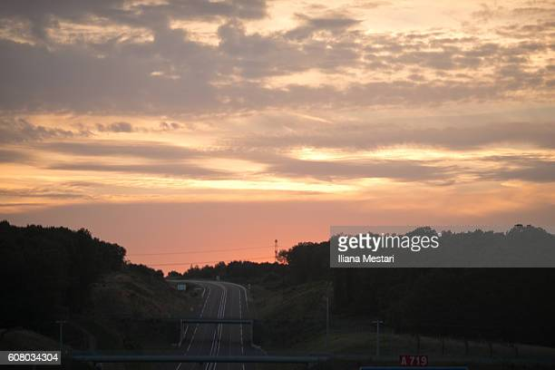 highway at sunset - allier stock photos and pictures