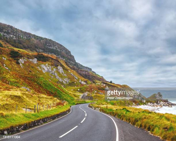 highway at the causeway coastline in northern ireland - coastline stock pictures, royalty-free photos & images